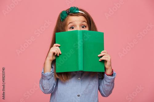Fotografie, Obraz  Cute girl 5-6 years wearing hair hoop having fun while reading interesting book