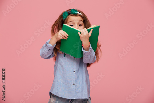 Image of amusing girl 5-6 years with long auburn hair reading interesting book h Wallpaper Mural