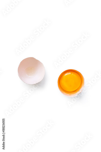 fresh brown organic chicken egg broken with yolk and egg white isolated on white background. Vertical composition. Top view