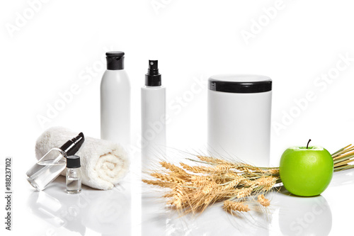 Keuken foto achterwand Spa Spa cosmetics, jar of cream, oil with wheat, white cosmetic bottles with apple and wheat towel, candle, soap isolated on white. Without label.