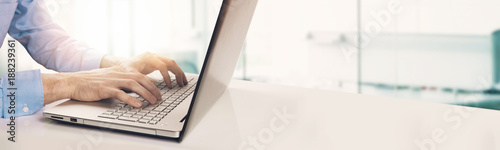 Fotografía  modern businessman typing on laptop keyboard in bright sunny office