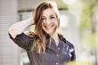 canvas print picture - junge Frau mit Piercings und Jeanskleid greift sich lachend ins Haar