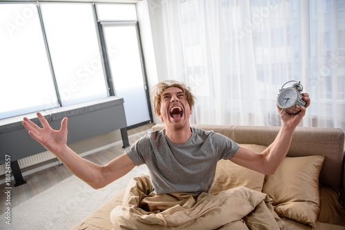 Photo Furious guy sitting on bed with angry expression and holding the alarm clock in hand