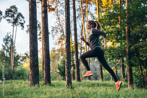 Foto  Young female athlete jogging in forest