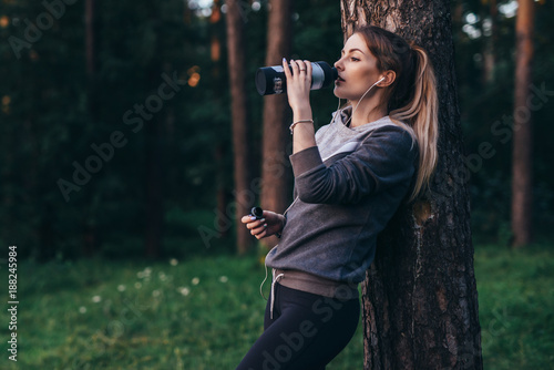 Fotomural Female jogger recovering after intensive workout standing near the tree drinking