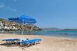 Blue deckchairs under parasol on the greek beach