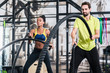 People doing functional training with battle rope in crossfit gym
