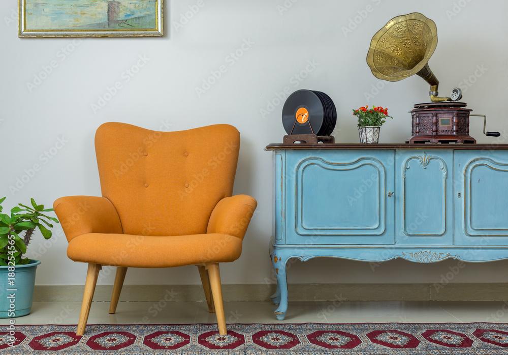 Fototapeta Vintage interior of retro orange armchair, vintage wooden light blue sideboard, old phonograph (gramophone), vinyl records on background of beige wall, tiled porcelain floor, and red carpet