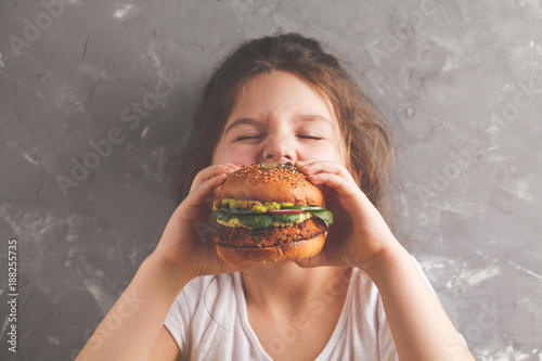 Deurstickers Kruidenierswinkel The little girl is eating a healthy baked sweet potato burger with a whole grains bun, guacamole, vegan mayonnaise and vegetables. Child vegan concept, gray background.