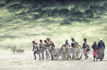 Napoleonic Soldiers And Women Marching And Pulling A Cannon In Plain Land, Countryside With Stormy Clouds. Soldiers Going Towards A Damaged Abonded House. Coming Home