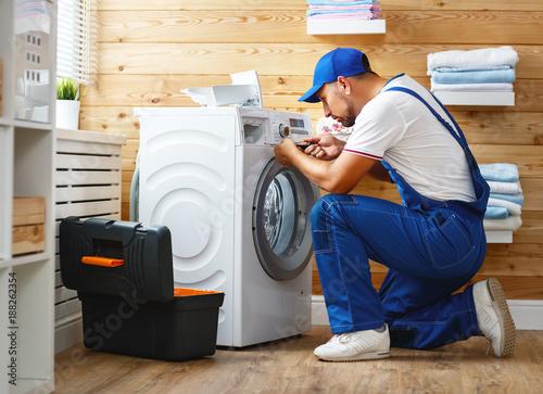 working man   plumber repairs  washing machine in   laundry Wallpaper Mural