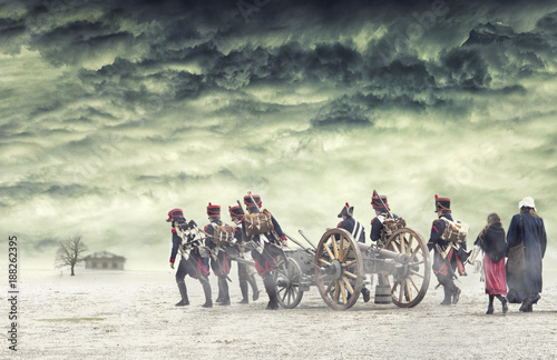 Fotografija  Napoleonic soldiers and women marching and pulling a cannon in plain land, countryside with stormy clouds