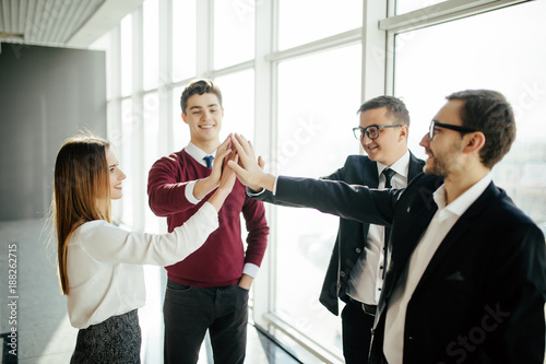 The four business people greeting with a high five against office the four business people greeting with a high five against office background m4hsunfo