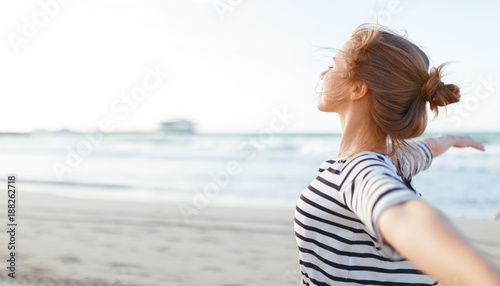 Deurstickers Ontspanning happy woman enjoying freedom with open hands on sea
