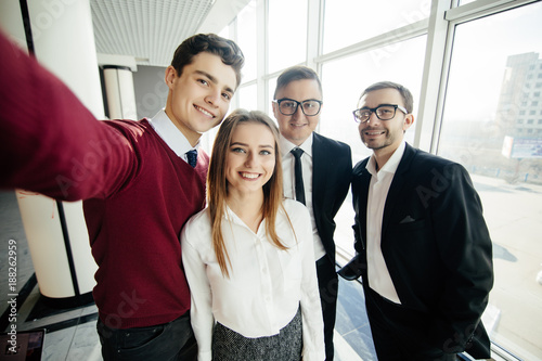 Fototapety, obrazy: Happy co-workers makes selfie. Three laughing young business people makes selfie with the sell phone in office