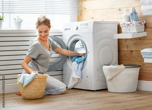 Happy housewife woman in laundry room with washing machine Canvas Print