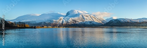 Poster Bleu landscape view of scotland and ben nevis near fort william in winter with snow capped mountains and calm blue sky and water