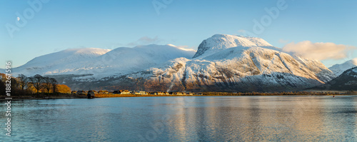 Aluminium Prints Blue landscape view of scotland and ben nevis near fort william in winter with snow capped mountains and calm blue sky and water