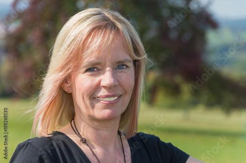 Photo Porträt einer Blonde Frau im Sommer mit schwarzem Shirt sieht nach rechts