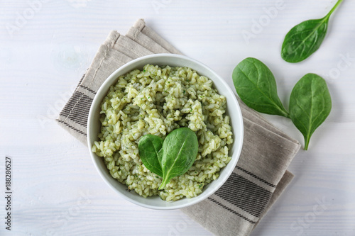Dish with delicious spinach risotto on wooden table
