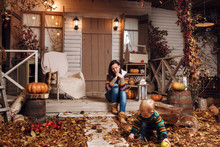 Cute Little Baby Boy And Mother Dressed In A Sweater, Jeans Playing Near House With Plush Toy Teddy Bear In Autumn Time. Woman And Son On Courtyard, Lit By Flashlights, With Dry Fall Leaves, Pumpkins.