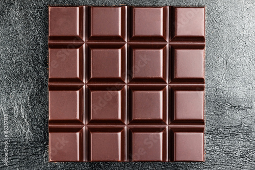Dark, bitter chocolate bar on black leather texture background, top view Canvas Print