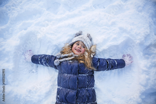 Poster Glisse hiver Beautiful little girl wearing navy jacket and knitted hat playing in a snowy winter park. Child playing with snow in winter. Kid play and jump in snowy forest. Family vacation with child in mountains