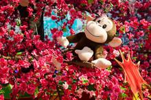 A Monkey Toy Sits On A Tree.
