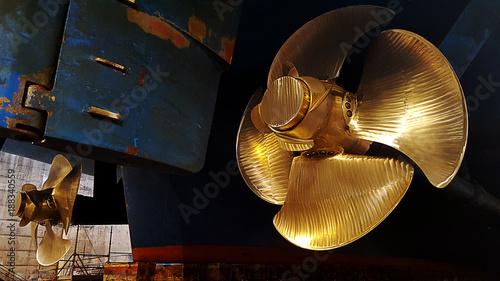 Foto  black ship hull and golden propeller at drydock