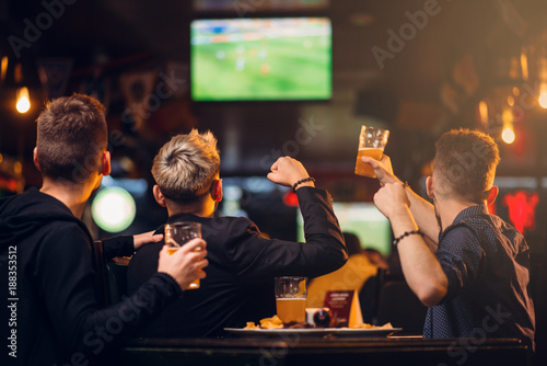 Fotografie, Tablou  Three men watches football on TV in a sport bar
