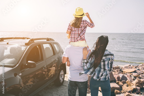 Fototapeta Happy family standing near a car on the beach. Happy family on a road trip in their car. Dad, mom and daughter are traveling by the sea or the ocean or the river. Summer ride by automobile obraz