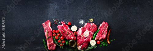 Foto op Canvas Vlees Raw fresh meat steak with cherry tomatoes, hot pepper, garlic, oil and herbs on dark stone, concrete background. Banner.