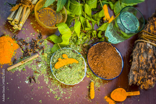 Photo  Powder of Indian lilac,Azadirachta indica in a glass plate with its leaves and raw underpowered turmeric