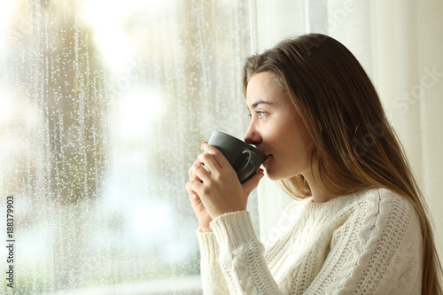 Teen drinking coffee looking through a window a rainy day