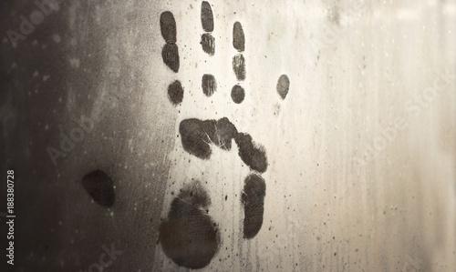 Valokuva  A handprint on the misted-on window