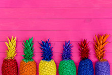 Row Of Colorful Painted Pineapples On Vivid Pink