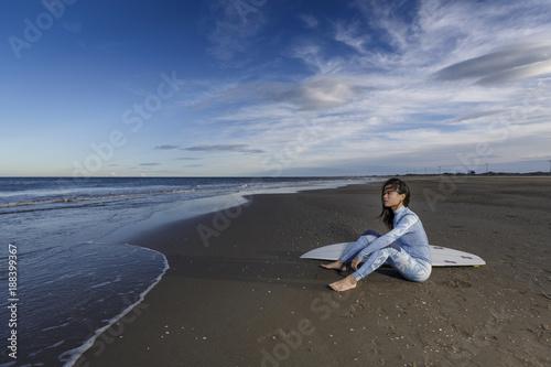Fotografía Mujer joven oriental cerca del mar tabla de surf