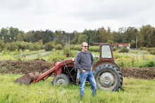 Man Standing Near Tractor In Countryside