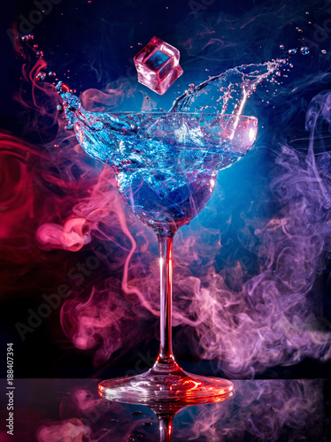 Foto op Plexiglas Cocktail ice cube falling into splashing cocktail on smoky background
