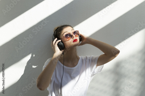 Papiers peints Magasin de musique Woman wearing sunglasses listening music while standing against white wall