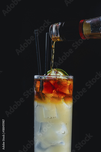 Close up of drink being poured in glass against black background