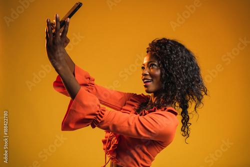 Cheerful black woman taking selfie