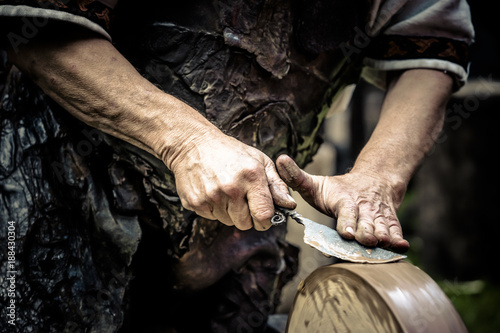 Fotografie, Obraz  Mann beim Messer schärfen an der Schleifscheibe