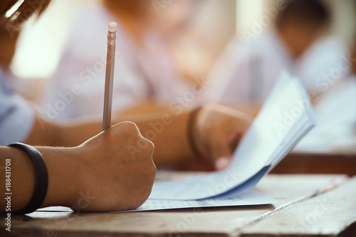 Fotomural Closeup to hand of student  holding pencil and taking exam in classroom with stress for education test