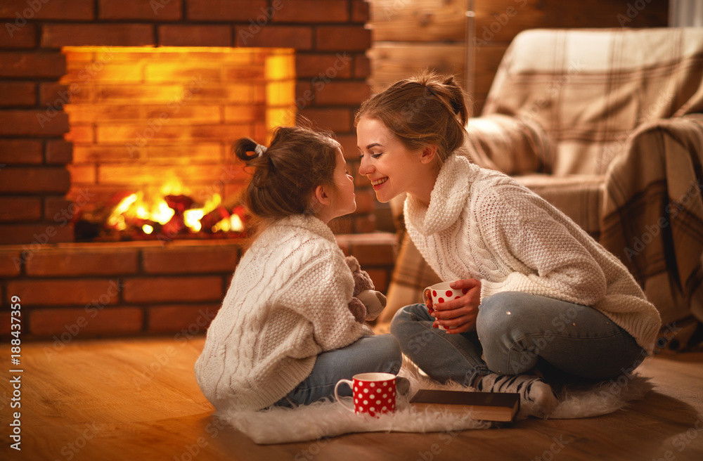Fototapeta family mother and child drinking tea and laughing on winter evening by fireplace.