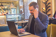 Businessman working in laptop and talking on cellphone in cafe