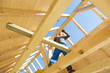 Carpenter roofer at work with wooden roof construction.