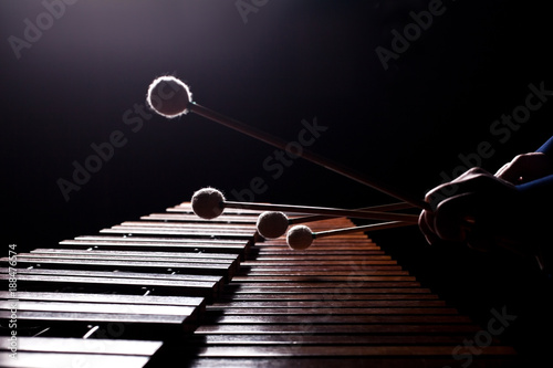 Photo  The hands of a musician playing the marimba in dark tones