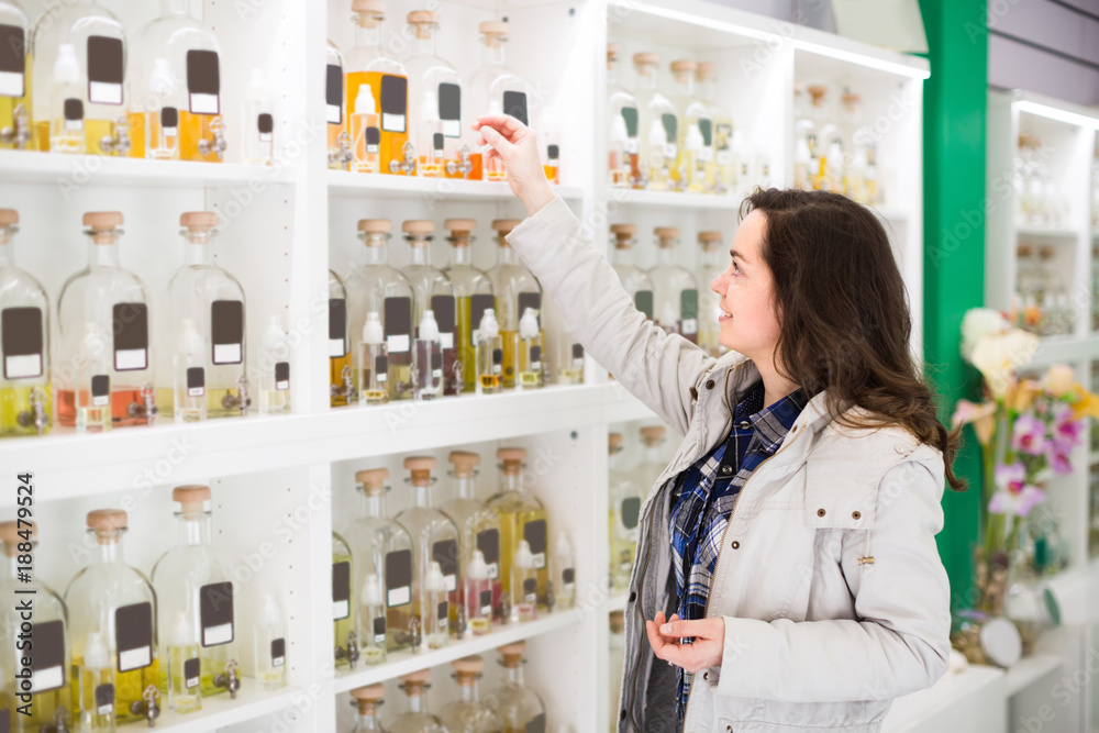 Fototapety, obrazy: Girl buying perfume in fragrance boutique.