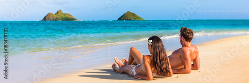 Hawaii travel summer vacation couple on hawaiian tropical beach in Lanikai, Oahu, Hawaii, US. American tourists people on holidays lying down, panoramic banner crop with moke islands in background. - 188479732